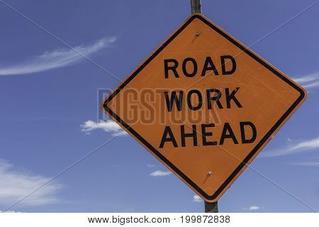 Road Work Ahead Sign shown against a bright blue sky