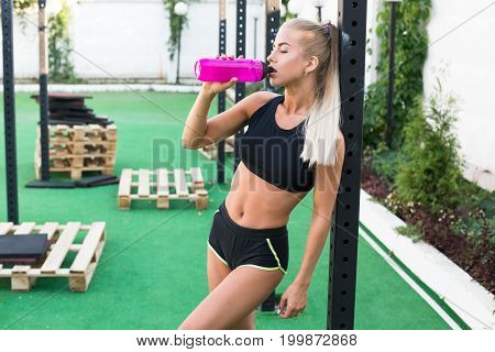 Attractive young woman in short shorts and top posing near playground and drink water. Sexy blond girl with bottle of water. Hot workout. Long hair of beautiful woman.