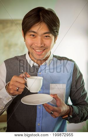 good looking asian man toothy smiling face happiness emotion with hot coffee cup ready to drink in hand
