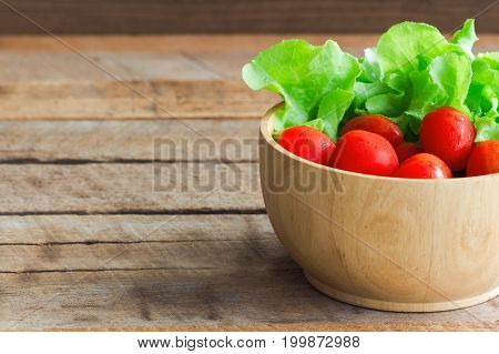 Fresh tomato and lettuce in wood bowl put on wood table. Side view of tomato and green oak lettuce with copy space for background. Fresh green oak lettuce and tomato prepare for cooking. Fresh vegetable concept for background.