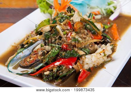 Spicy Stir-fried With Seafood On White Plate On Wood Table In Restaurant. Thai Style.