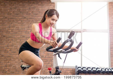woman smile happily and use exercise bike