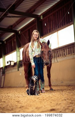 Young Cowgirl With Her Horse And Dog in indoors riding arena
