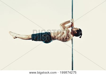 Young strong pole dancing man on wall background. Soft sepia tint.