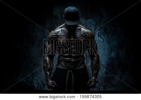 Young strong man bodybuilder in cap on stone wall background. Dramatic dark contrast colors.
