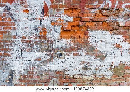 old wall of broken brick smeared with white paint. grunge textured background