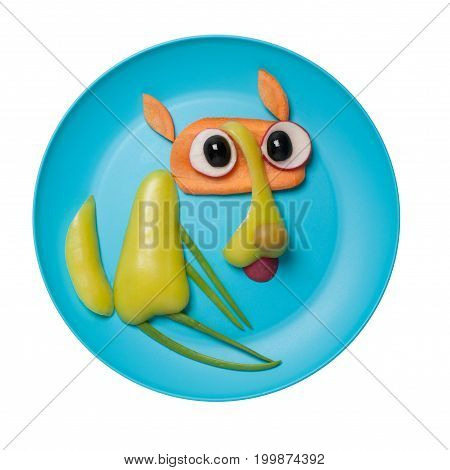 Funny sitting wolf compiled of vegetables on plate