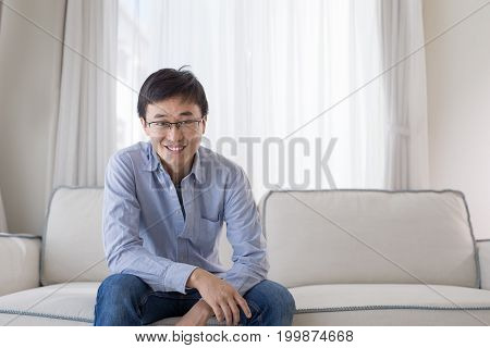 man smile happily and sit on sofa at home