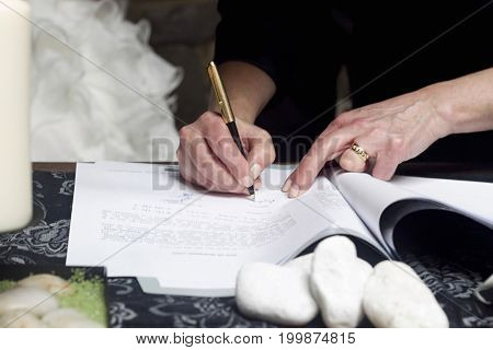 A witness signing the formal documents in a wedding