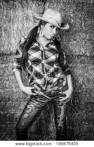 Cowgirl wearing hat holding gun