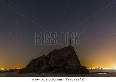 Silhouette of a person standing on the top of the large Currumbin Rock Gold Coast, shining a torch under a starry night sky.