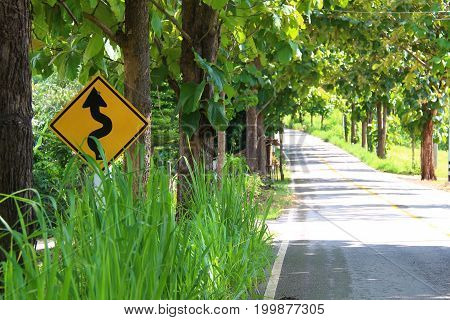 The black and yellow caution sign of winding road ahead of the rural road with 2 sides framed by trees