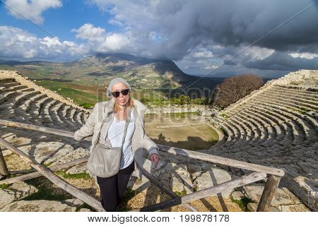 Female tourist taking photo in front of greek theater of Segesta, Sicily, Italy