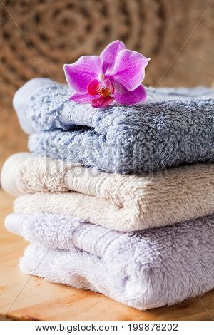 Bath Towel Set On Wooden Background With Orchid