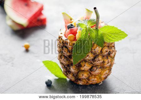 Exotic Fruit Salad Served In Half Pineapple On Dark Background