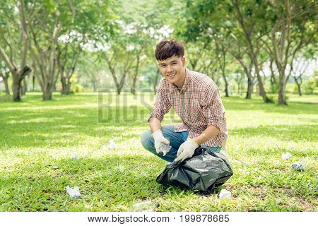 Young asian man holding black bin bag and putting plastic household waste into it