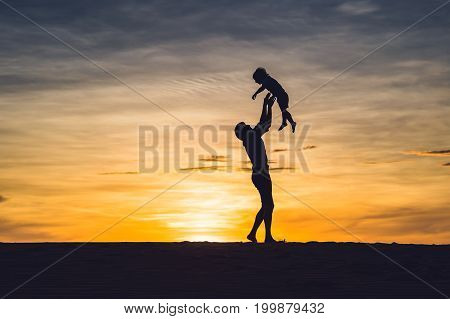 Father And Son At The Red Desert At Dawn. Traveling With Children Concept