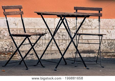 one empty table and two empty chairs for an interior of summer cafe on the street or for a summer garden