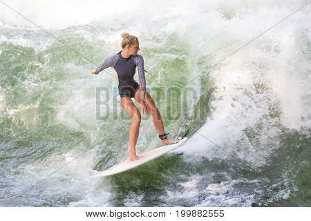 Atractive sporty girl in neoprene shorty surfing on famous artificial river wave in Englischer garten, Munich, Germany.