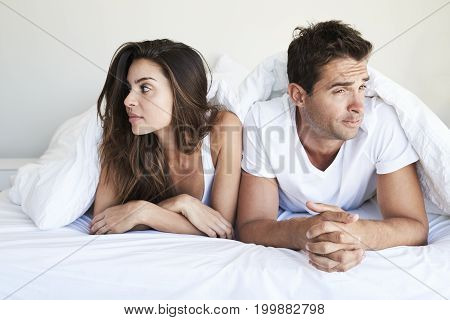 Awkward couple lying in bed looking away