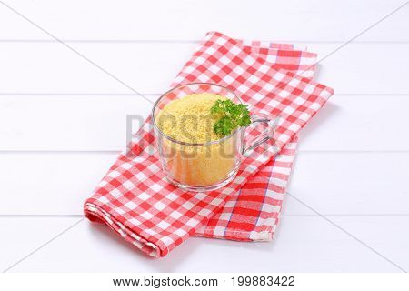 cup of raw couscous on checkered place mat