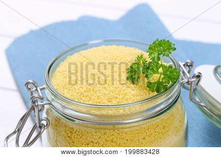 jar of raw couscous on blue place mat - close up
