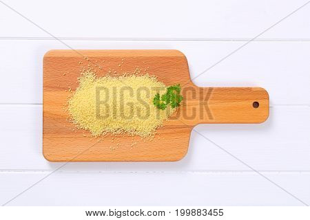 pile of raw couscous on wooden cutting board