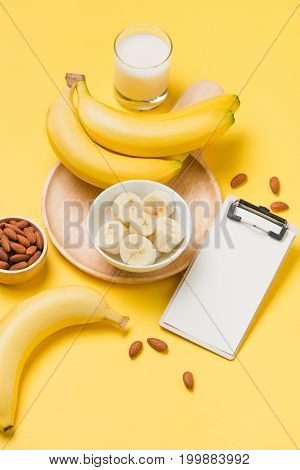 Banana And Milk On Yellow Paper Background With Blank Clipboard For Text