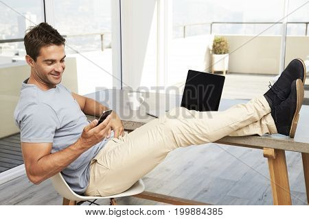 Smiling guy texting from desk at home