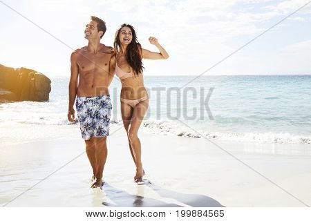 Good looking vacationing couple on beach smiling