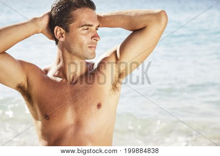 Hunky dude at beach posing and looking away
