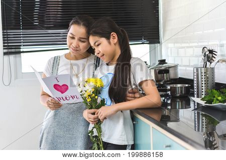 Mom reading leather postcard and children girl holding flower bouquet in home family lover or mother day happiness concept.