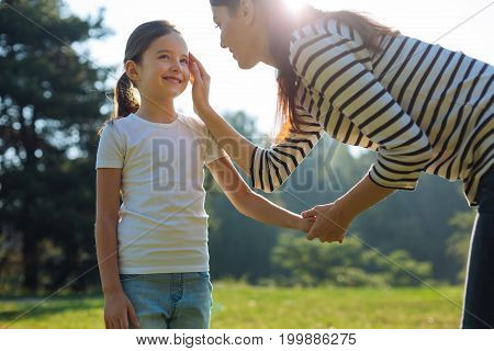 Motherly fondness. Gentle young mother holding her daughters hand and lovingly touching her cheek during the walk in the park