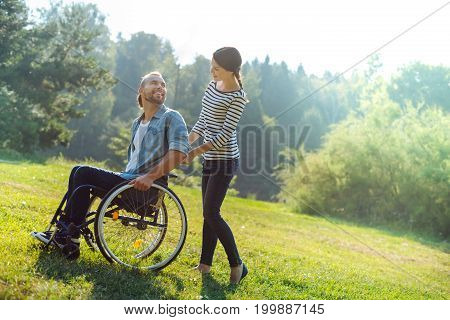 Enjoying walk. Caring young wife carrying her beloved husband in a wheelchair during a walk in the meadow while he looking at her lovingly