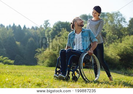 Affectionate looks. Charming young woman carrying her incapacitated husband in a wheelchair and exchanging fondly looks
