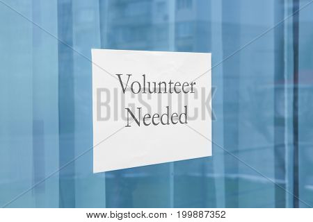 Sheet of paper with text VOLUNTEER NEEDED on window glass
