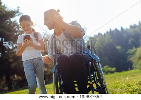 Best time together. Charming smiling little girl standing near her father sitting in a wheelchair and listening to music with him while sharing one pair of headphones