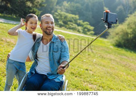 Goofing around. Charming little girl hugging her upbeat father sitting in a wheelchair and posing with him for a selfie while making funny faces