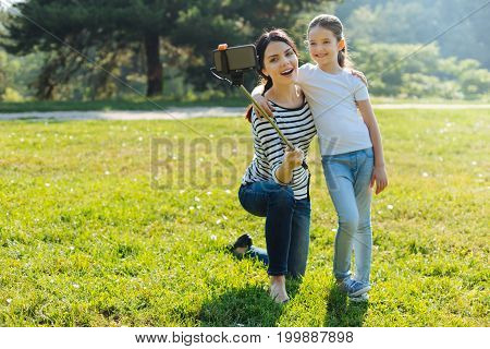 Lovely photo. Charming pleasant young mother and her daughter hugging each other and taking a selfie in the park, using a selfie stick