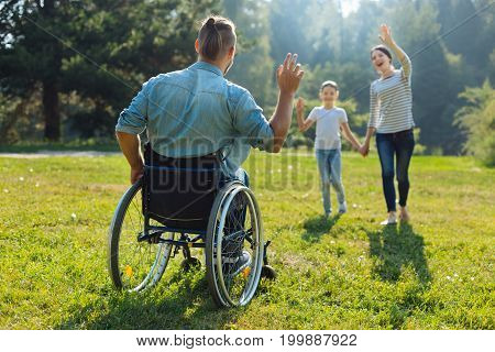 Hey there. Young man with disabilities sitting in a wheelchair outdoors and waving hello to his wife and daughter approaching him