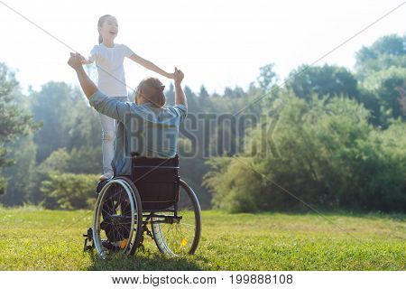We love life. Happy little girl standing on the lap of her beloved father sitting in a wheelchair, holding his hands and smiling broadly