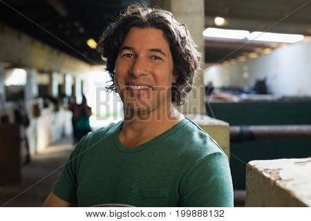 Portrait of happy man standing in the stable