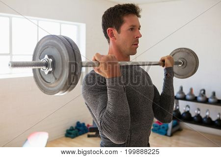 Male athelte lifting barbell at gym