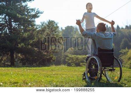 Precious moment. Young father with mobility impairment sitting in the wheelchair in the park and holding his little daughter standing on his lap and smiling broadly