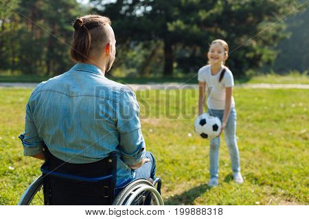 Favorite game. Back view of a young man with mobility impairment sitting in a wheelchair and playing ball with his cheerful little daughter in the park