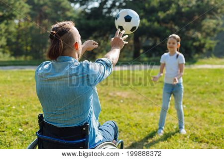 Cheerful game. Back view of a young man with mobility impairment passing a ball to his little daughter while playing a game with her in the park