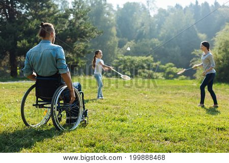 Enjoying sports. Pleasant young man with mobility impairment sitting in the wheelchair and watching his family play badminton in the meadow