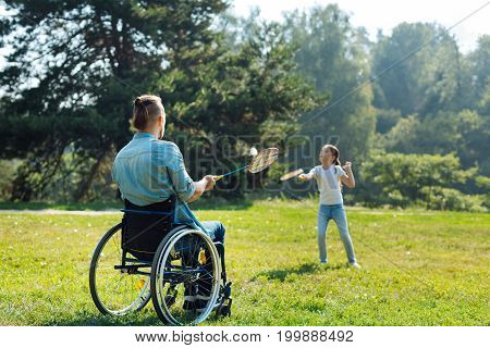 Favorite kind of sport. Young father with disabilities sitting in the wheelchair and playing badminton with his daughter while having a walk in the park