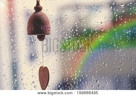 Vintage Image Of Small Wooden Bells On The Window With Blurred Rain Drops And Light Nature Backgroun