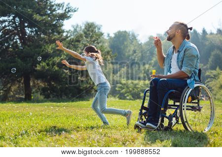 Enjoying active weekend. Pleasant upbeat young man with disabilities sitting in the meadow and blowing soap bubbles while his daughter running after them